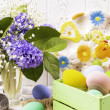 Colorful Easter eggs in a green box and rabbit fig...
