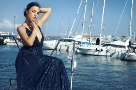 Photo for Pretty young woman in elegant glitter dress posing on yacht, outdoor fashion portrait - Royalty Free Image