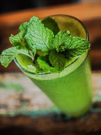 Photo pour Smoothie vert avec feuilles de menthe sur fond bois - image libre de droit