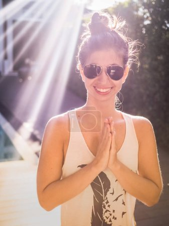 Photo for Beautiful young woman greeting with namaste gesture - Royalty Free Image