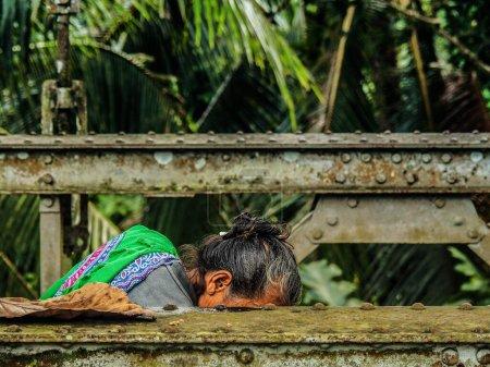 Photo pour Vieille femme travaillant dans le parc pendant la journée - image libre de droit