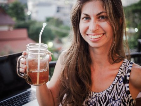 Photo for Beautiful young woman holding glass jar of tea - Royalty Free Image
