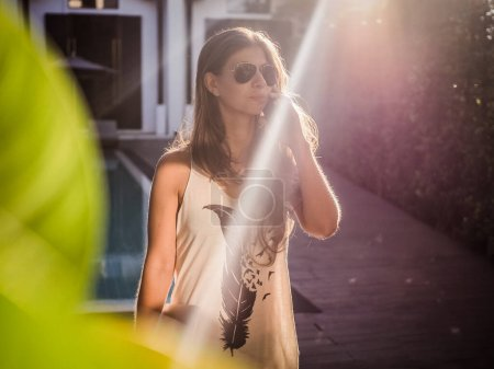 Photo for Beautiful young woman talking on smartphone while standing on street - Royalty Free Image