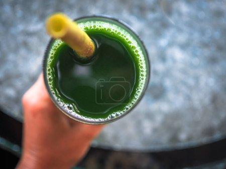 Photo pour Main féminine tenant cocktail vert dans un verre - image libre de droit