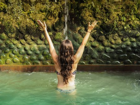 Photo for Back view of young woman relaxing in water, Bali - Royalty Free Image