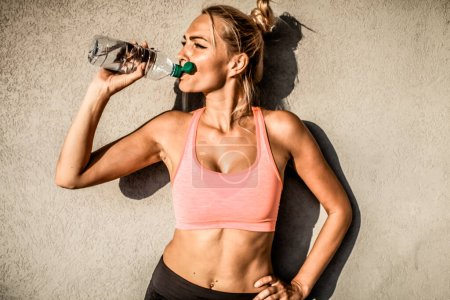 Photo pour Jeune sportive avec bouteille d'eau sur fond gris - image libre de droit