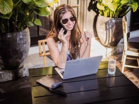 Photo for Beautiful young woman talking on smartphone while sitting at cafe with a laptop - Royalty Free Image