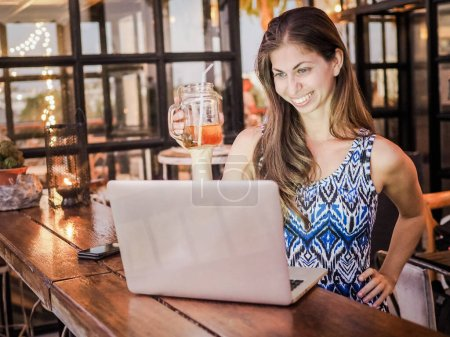 Photo for Happy beautiful young woman using laptop computer in cafe - Royalty Free Image