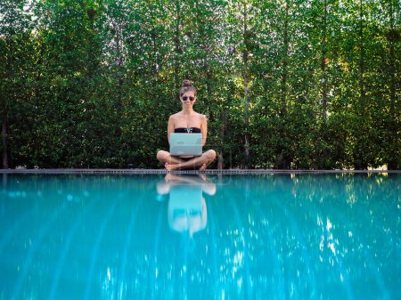 Photo for Young woman in bikini sitting on the edge of the pool with laptop - Royalty Free Image