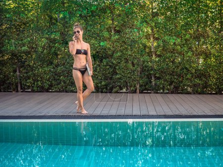 Photo for Young woman in bikini on the edge of the pool with laptop - Royalty Free Image