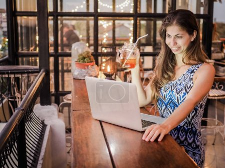 Photo pour Beautiful woman  working on laptop at table in restaurant - image libre de droit