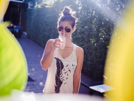 Photo for Young woman in sunglasses drinking water - Royalty Free Image