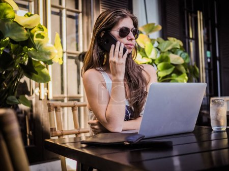 Photo pour Pretty brunette woman in cafe drinking tea and using laptop while working in the bar - image libre de droit