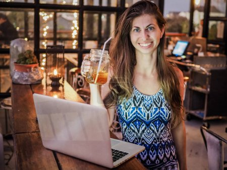Photo pour Happy beautiful young woman using laptop computer in cafe, drinking cocktail - image libre de droit