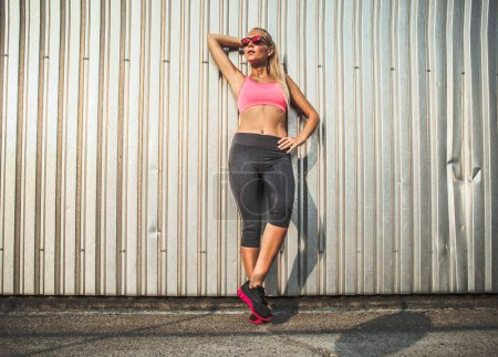Photo for Young woman in sportswear with a skateboard in the city - Royalty Free Image