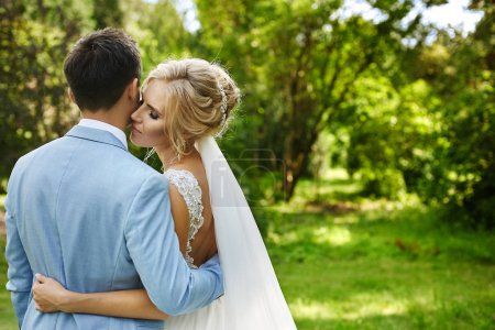 Beautiful and fashionable blonde model girl with bright makeup and with luxury jewelry in her stylish hairstyle, in fashionable dress hugs her men and posing with closed eyes at open air