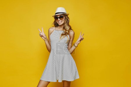Beautiful and fashionable blonde model girl with sexy body and with charming smile, in white striped dress, in stylish hat and in trendy sunglasses posing at yellow background
