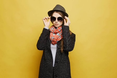Photo for Fashionable and beautiful blonde model girl in stylish coat with leopard patterns and in trendy hat adjusting her fashionable sunglasses and posing at yellow background. - Royalty Free Image