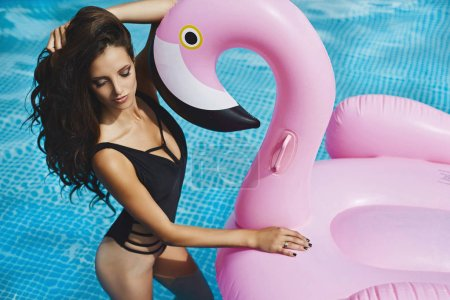 Photo for Sexy and fashionable brunette girl with pink flamingo in the swimming pool. - Royalty Free Image
