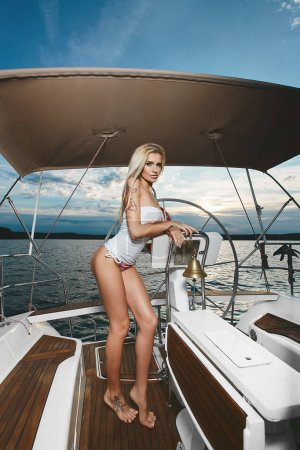 Photo for Sexy and fasionable long-legged blonde model girl with perfect body in bikini and white t-shirt posing near steering wheel on a yacht ship at the sea. - Royalty Free Image