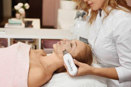 Photo pour Belle femme se faire éplucher le visage procédure dans une clinique de beauté, procédure de lifting non chirurgical. Traitement facial rajeunissant - image libre de droit