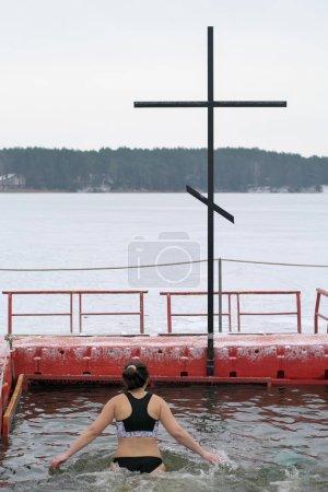 Photo pour La fille plonge dans le trou, l'hiver, la tradition orthodoxe, le baptême du Christ. Lac en Europe de l'Est - image libre de droit