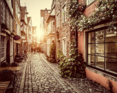 Beautiful view of old town in Europe in golden evening light at sunset in summer with pastel toned retro vintage Instagram style grunge filter and lens flare sunlight effect