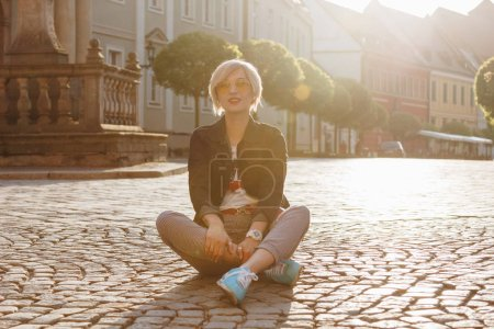 beautiful young woman sitting on cobbles on wroclaw street, poland