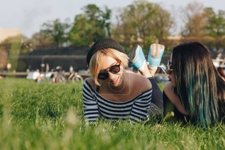 beautiful young women lying on grass in park and chatting