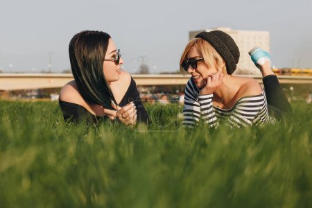 happy young women lying on grass in park and chatting