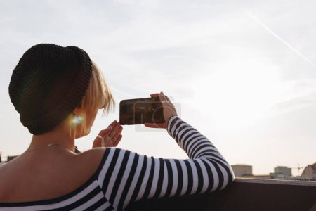 rear view of young woman in striped shirt taking photo with smartphone in front of sunset sky