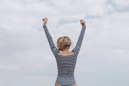 rear view of young woman in striped bodysuit with raised arms on cloudy day