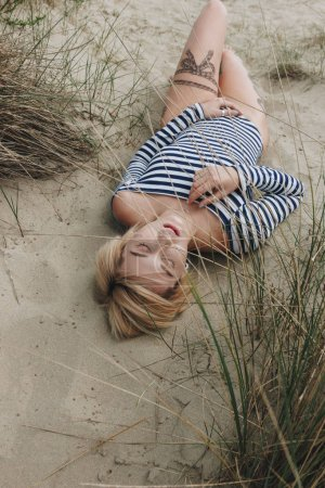 high angle view of sensual young woman in striped bodysuit lying on sand