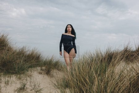 attractive young woman in black bodysuit on sand dune under cloudy sky