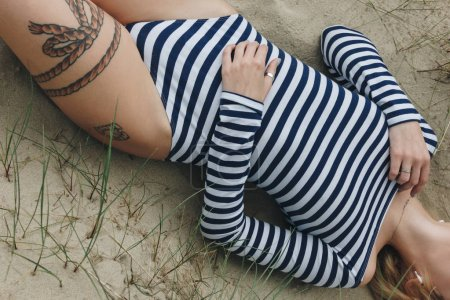 cropped shot of woman in striped bodysuit lying on sand