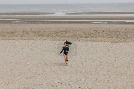 attractive young woman in black bodysuit running on sandy seashore