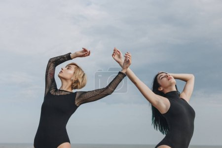 sensual young women in black bodysuits dancing in front of cloudy sky