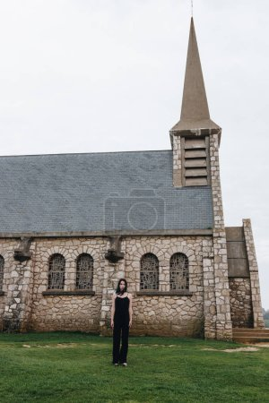 attractive young woman standing on green grass in front of ancient church