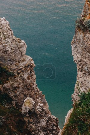 high angle view of beautiful rocky cliffs with blue sea on background, Etretat, France