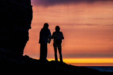 silhouettes of travellers couple standing on rocks in front of sunset
