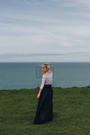 elegant stylish girl posing on majestic cliff, Etretat, Normandy, France