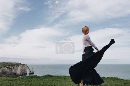 Photo for Beautiful fashionable girl posing on cliff, Etretat, Normandy, France - Royalty Free Image