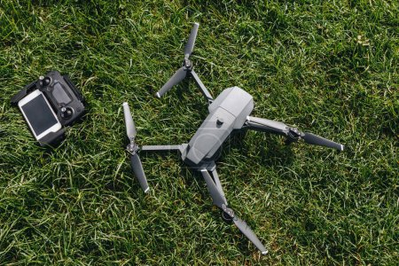 Photo for Top view of drone and controller with smartphone on green grass - Royalty Free Image