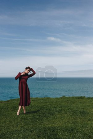 Photo for Elegant attractive young woman posing on cliff near the sea, Etretat, Normandy, France - Royalty Free Image