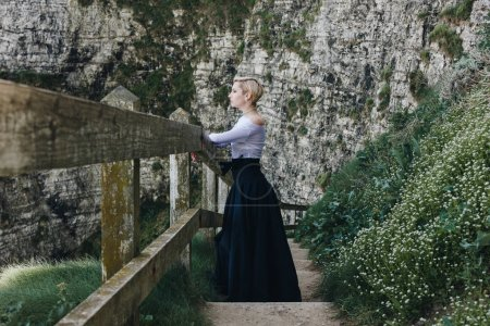 Photo for Elegant girl posing on stairs with wooden railings on rocky cliff, Etretat, Normandy, France - Royalty Free Image