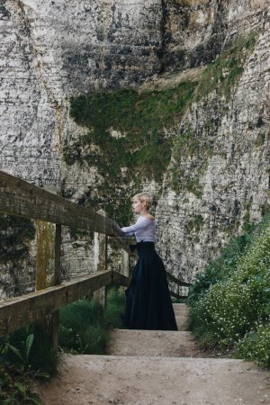 beautiful girl standing on stairs with wooden railings on rocky cliff, Etretat, Normandy, France
