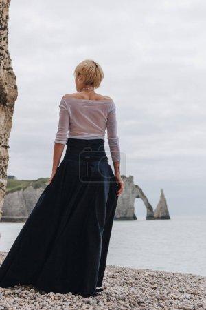 Photo pour Vue arrière de la fille élégante à la mode sur le rivage près des falaises et de la mer, Etretat, Normandie, France - image libre de droit