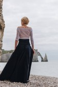 rear view of fashionable elegant girl on shore near cliffs and sea, Etretat, Normandy, France