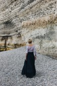 rear view of elegant girl walking on shore near cliff, Etretat, Normandy, France