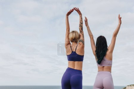 Photo for Back view of girls posing in stylish sportswear, Etretat, Normandy, France - Royalty Free Image
